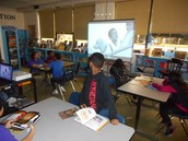Students reviewing video Book Reviews for books that will be on sale at the Book Fair