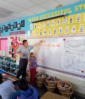 Sr. Aguirre ayuda a sus alumnos de tercer grado a entender la geometría.