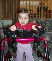 Child with Rett's Syndrome using a walker to assist her walking.