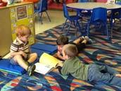 Gavin, Wyatt, and Trey look through a book together