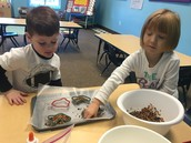 Sawyer and Elle making their bird seed ornaments