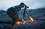 here is a man taking a picture of lava