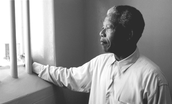 Nelson Mandela looks out of the cell he was imprisioned in.