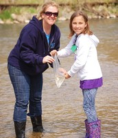 Mrs. Yeloushan assists Avery Pate (3rd grade) with the release of her salmon.