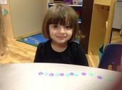 Tess making a purple green star pattern