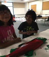 Children using a real silver salmon to make a print