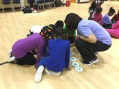 Mrs. Jones helping a team count their coins.