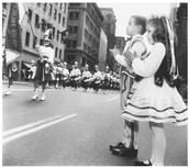 A girl and boy watching a parade