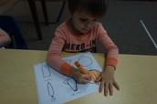 Landon is pressing hard with his crayon to get a nice dark orange pumpkin