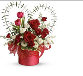 Often a heart will be made out of part of the arrangement to match the holidays theme of love.