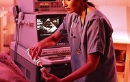 The Ultrasound technician is is using the  ultrasound gel on the transducer