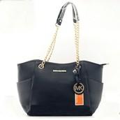 Descripción: La Bolsa negra y de color oro, es hecha de cuero.