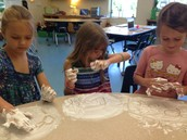Lucy, Siri, and Louisa spelling long vowel sound words in shaving cream.