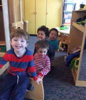 Darren, Walter, TJ and Charlie pretend to sled in the classroom