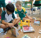 3TCo children using their patience to create a Rube Goldberg machine.