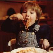 ילד קטן אוכל ספגטי עם רוטב