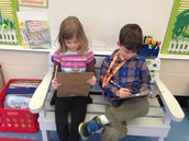 Camden and Bella use clipboards to work on the bench