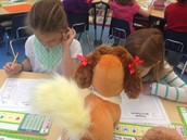 Bella and Julia showing their stuffed animals how hard they work.