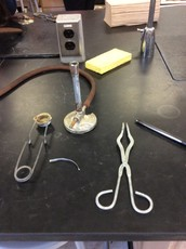 First set up a Bunsen burner, put of safety glasses, and get a set of tongs
