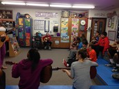 Sixth graders are learning to play the guitar.