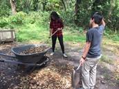 Nikko and Yakira load the wheelbarrow