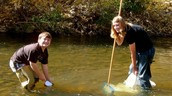 Two volunteers working together to clean up a part of the Colorado Watershed