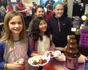 5th graders, Lucy, Kayla, Amaiya and Teel in Mr. Tomlinson's class take a break from party activites to grab a sweet Valentine treat.