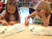 Lillie and Savanna reading about tadpoles turning into frogs.