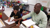 Paraprofessional Greg Jackson working with 2nd grade students