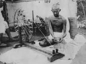 Gandhi taking part in sewing.