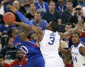 Kansas player shooting over Kentucky player