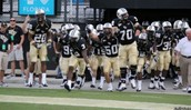 The UCF football team running out of the tunnel before a game