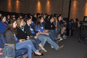 Students watching their peers present INOK