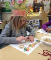 Making necklaces with one hundred pieces of cereal!