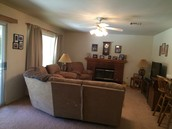 Large Family room with fire place and a wet bar.