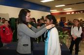 Sriya Kalluri  receiving her first place ribbon from Mrs. Wittmus