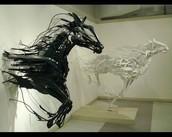 Os dois cavalos correndo para fora da parede