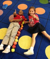 Joshua A. and Madeline are enjoying measuring with apples!