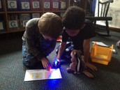 Flashlight reading to stuffed animals on Pajama Day!