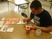 Student painting clay tiles