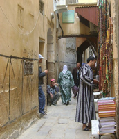 A man in an alley selling religious items.