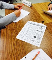 Ms. Brevard's students work on different reading stations while Ms. Brevard works with a small group on close reading.