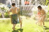 Kids running through the sprinkler