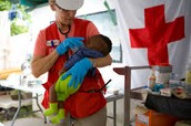 Red Cross caring to an infant