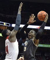 Central Florida basketball player, Isaiah Sykes, shoots over Louisville defender