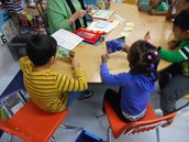 Students in Ginny Chaffee's K class using a mirror to watch their mouth as they say words