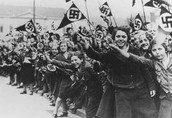 Members of the League of German Girls wave Nazi flags in support of the German annexation of Austria in Vienna, Austria, March 1938