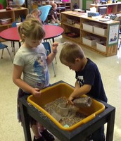 Zoey and Trey are filling the containers with rice