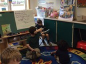 Shawn reading a book to Sriya and Joey.