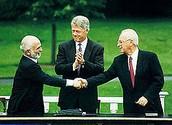 לחיצת יד בין חוסיין מלך ירדן ויצחק רבין, לצד נשיא ארצות הברית ביל קלינטון